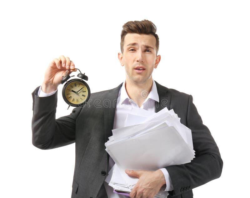 Homem de negócios incomodado com o despertador no fundo branco Conceito da gest?o de tempo imagens de stock royalty free