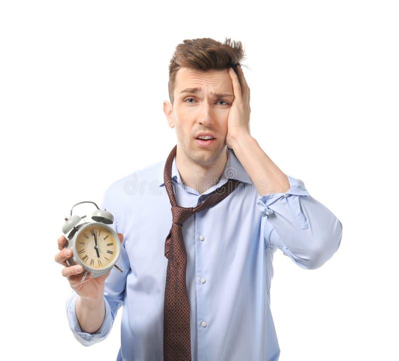 Homem de negócios incomodado com o despertador no fundo branco Conceito da gest?o de tempo foto de stock royalty free