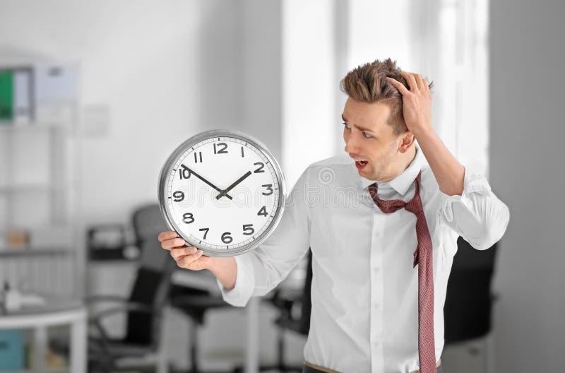 Homem de negócios incomodado com o pulso de disparo no escritório Conceito da gest?o de tempo foto de stock