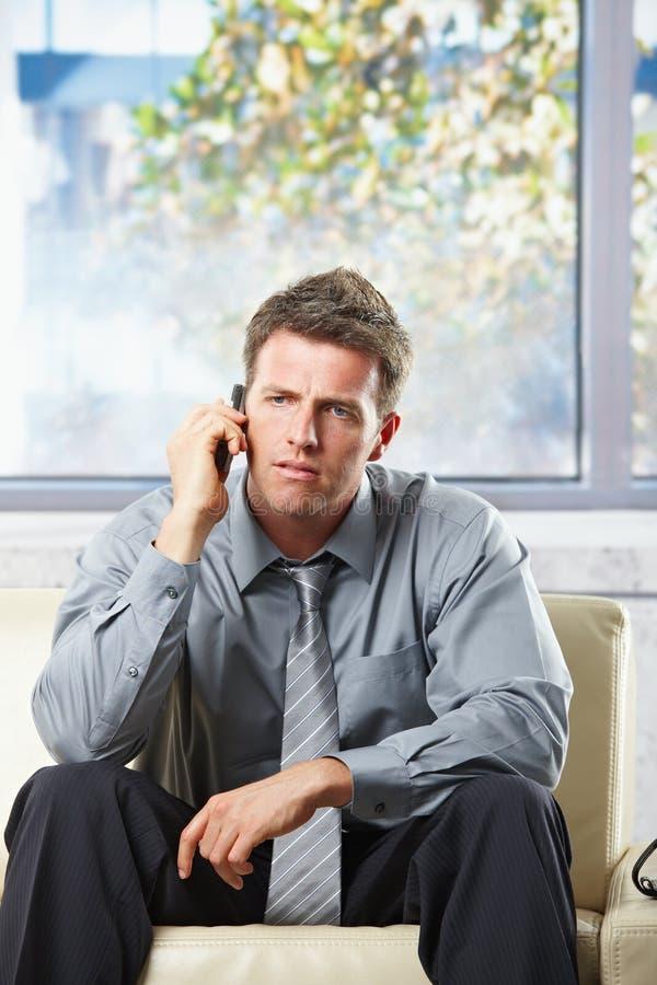 Homem de negócios incomodado no phonecall foto de stock