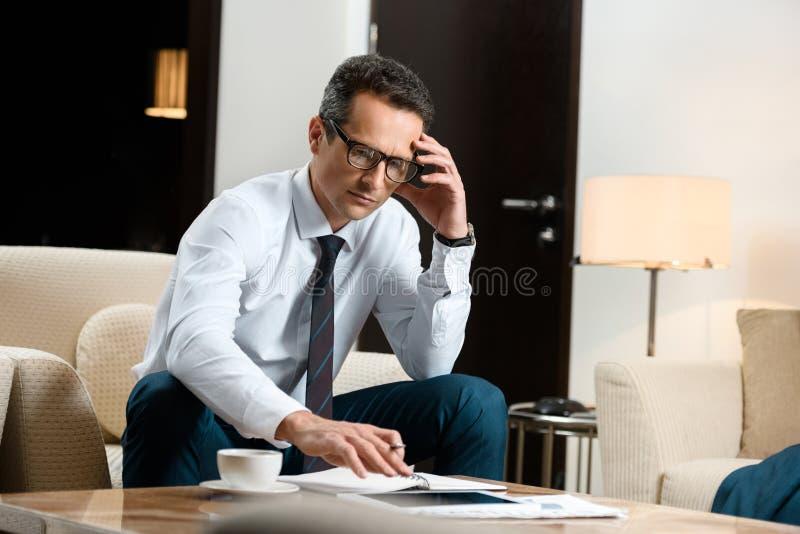 Homem de negócios incomodado no vestuário formal que senta-se na poltrona e no trabalho fotografia de stock royalty free