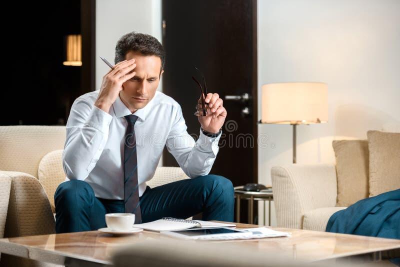 Homem de negócios incomodado no vestuário formal que senta-se na poltrona e no trabalho fotos de stock royalty free