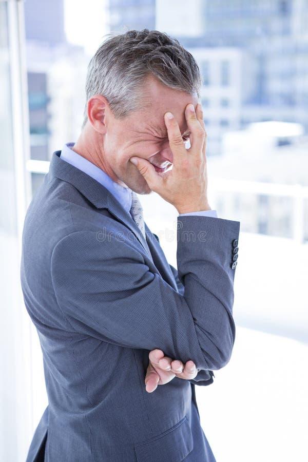 Homem de negócios incomodado que guarda sua cabeça imagem de stock