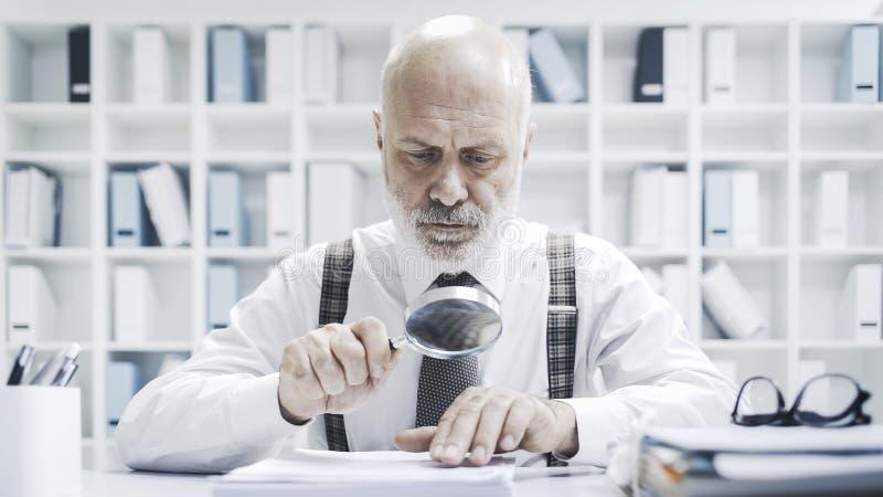 Homem de negócios incorporado que verifica o documento com uma lente de aumento imagem de stock
