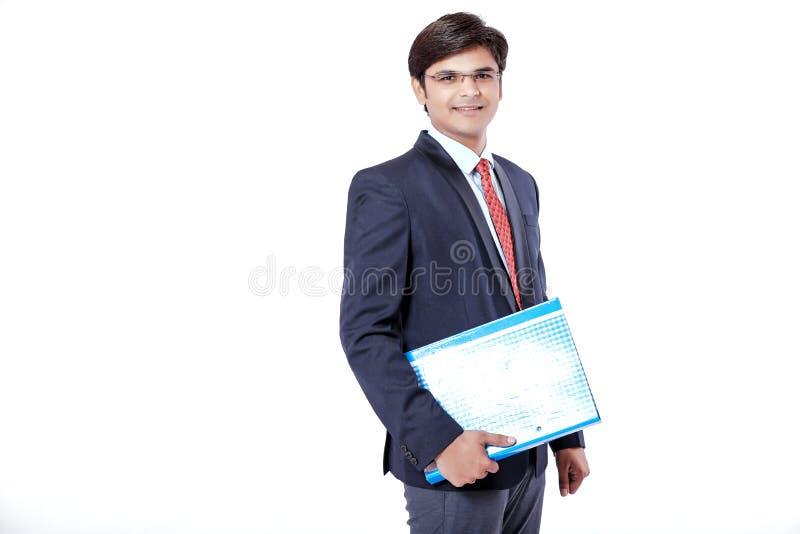 Homem de negócios indiano novo que guarda o arquivo de original sobre o fundo branco fotografia de stock