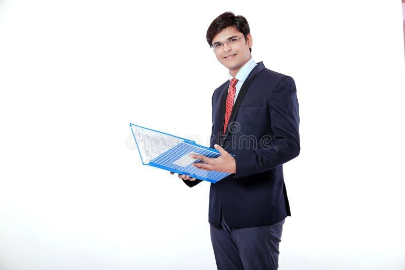 Homem de negócios indiano novo que guarda o arquivo de original sobre o fundo branco imagem de stock