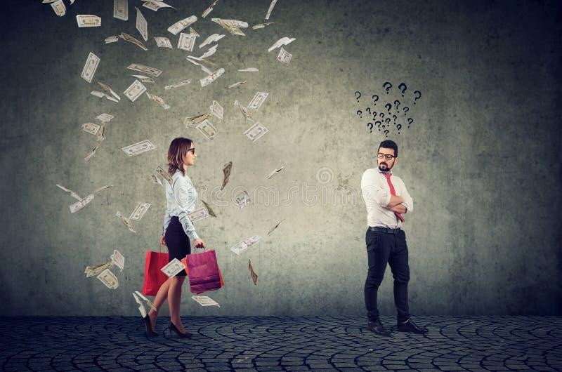 Homem de negócios intrigado olhando para uma mulher feliz compradora com sacos coloridos sob chuva de dinheiro fotos de stock royalty free