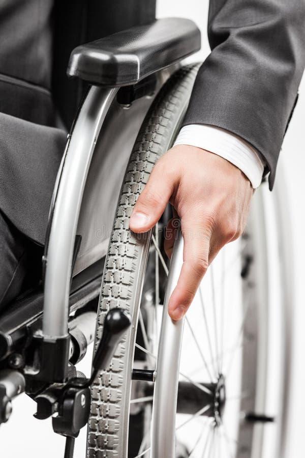 Homem de negócios inválido ou deficiente na cadeira de rodas de assento do terno preto fotografia de stock royalty free