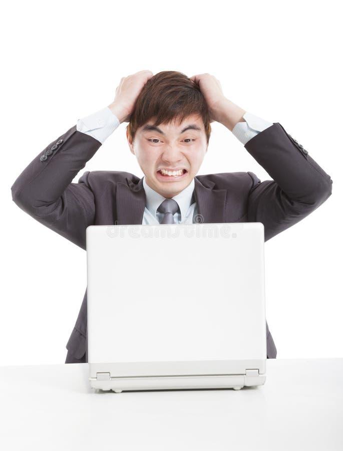 Homem de negócios irritado com um portátil fotos de stock