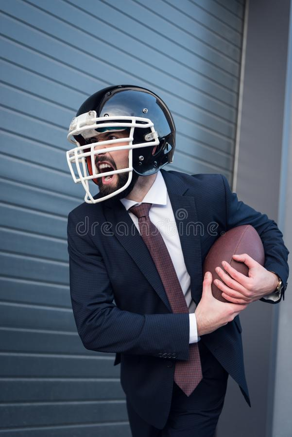 homem de negócios irritado novo no terno e capacete do rugby com a bola nas mãos imagens de stock royalty free