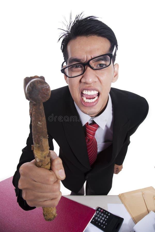 Homem de negócios irritado que bate com martelo foto de stock royalty free