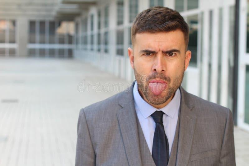 Homem de negócios irritado que cola sua língua para fora foto de stock