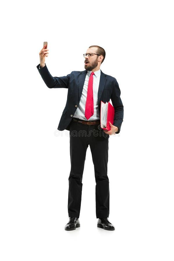 Homem de negócios irritado que fala no telefone isolado sobre o fundo branco no tiro do estúdio fotos de stock royalty free