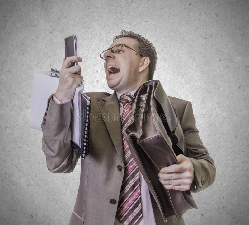 Homem de negócios irritado que grita no smartphone no fundo branco imagem de stock