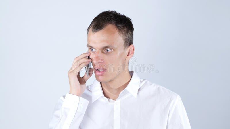 Homem de negócios irritado que obtém más notícias no telefone imagem de stock