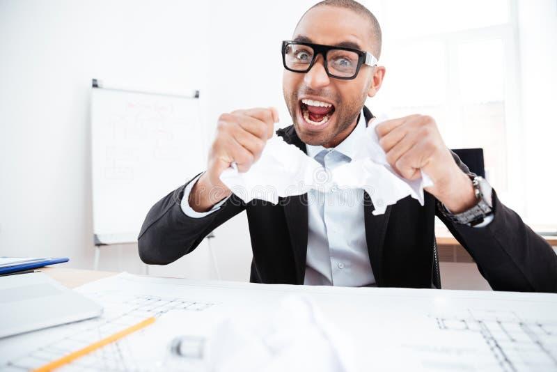 Homem de negócios irritado que rasga acima um original no escritório foto de stock