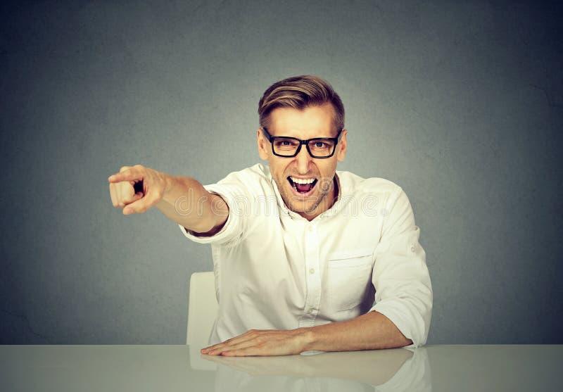 Homem de negócios irritado que senta-se na mesa que grita fotografia de stock