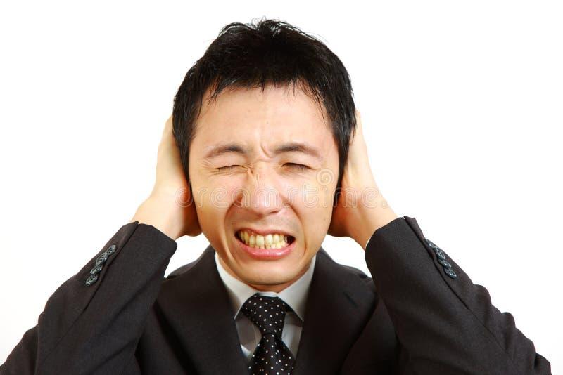 Homem de negócios japonês que guarda as mãos em suas orelhas, protegendo-se do ruído foto de stock