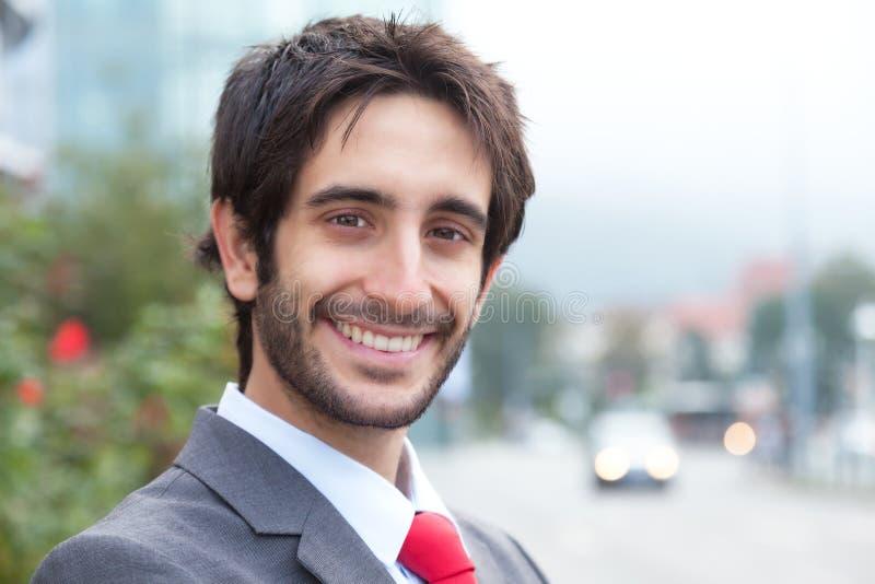 Homem de negócios latin de riso com a barba na frente de seu escritório imagem de stock royalty free