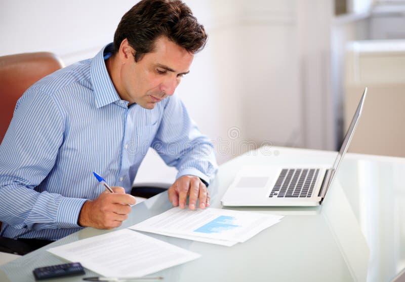 Homem de negócios latino-americano adulto que olha suas notas foto de stock royalty free