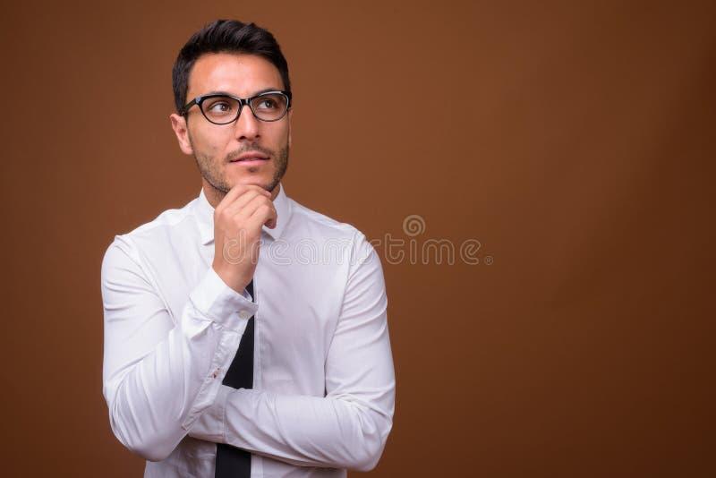 Homem de negócios latino-americano considerável novo contra o fundo marrom fotos de stock royalty free