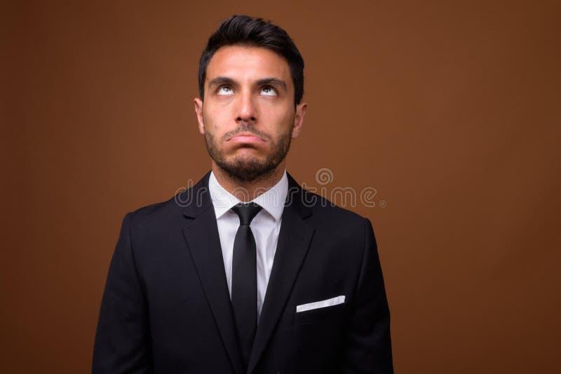 Homem de negócios latino-americano considerável novo contra o fundo marrom foto de stock