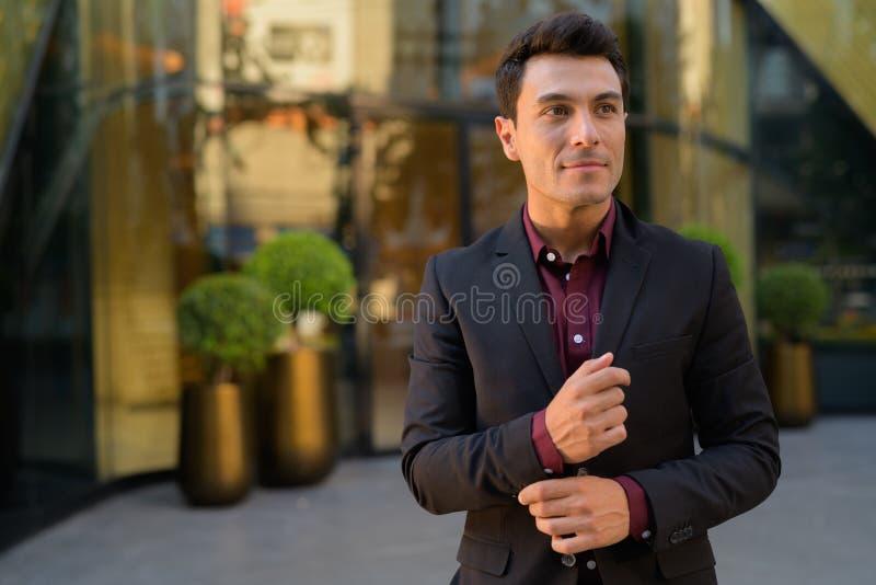Homem de negócios latino-americano considerável novo que pensa fora do prédio de escritórios fotografia de stock