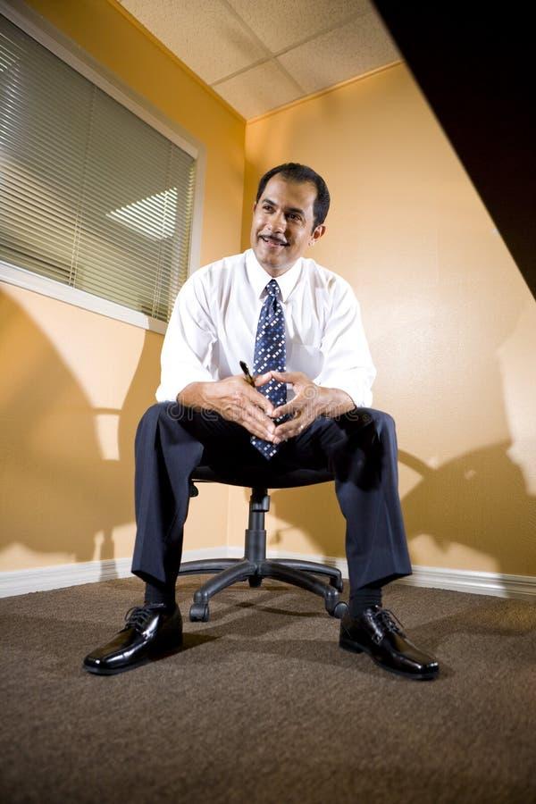 Homem de negócios latino-americano de meia idade que senta-se no escritório foto de stock