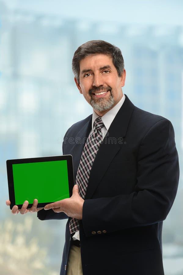 Homem de negócios latino-americano Displaying Electronic Tablet fotografia de stock royalty free