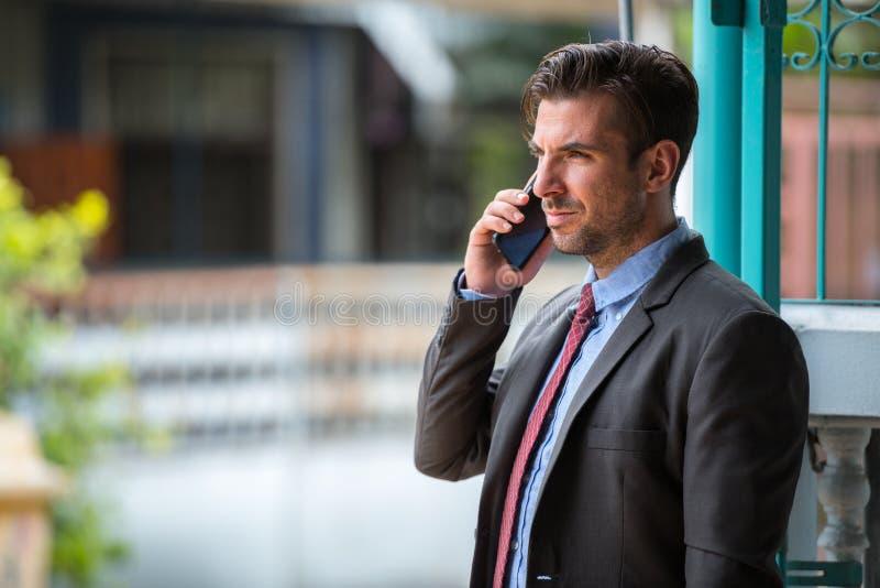 Homem de negócios latino-americano feliz novo que fala no telefone fora imagem de stock