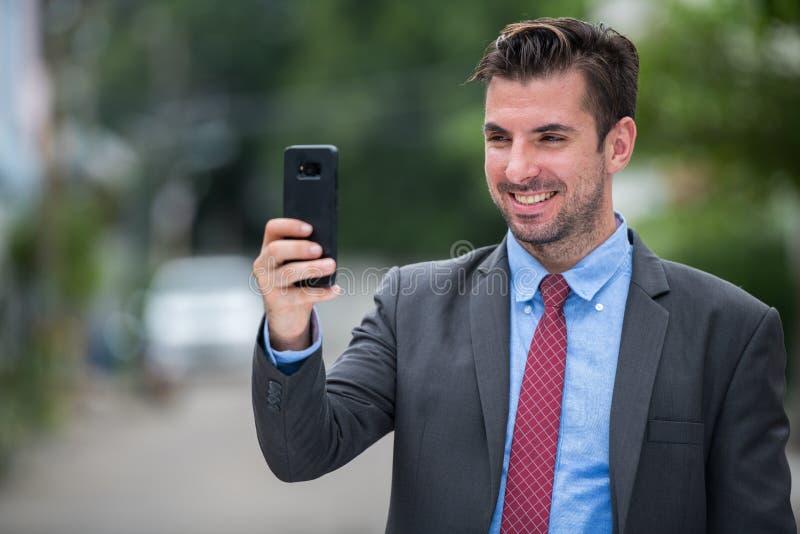 Homem de negócios latino-americano feliz novo que sorri ao usar o telefone fora fotos de stock royalty free
