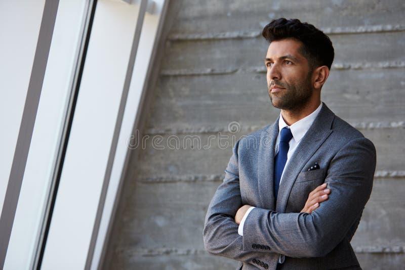 Homem de negócios latino-americano Standing Against Wall no escritório moderno fotos de stock royalty free