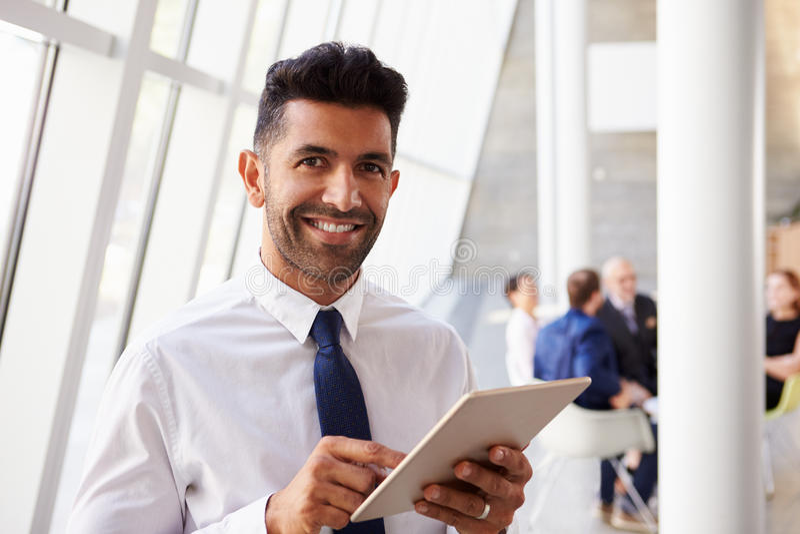 Homem de negócios latino-americano Using Digital Tablet no escritório moderno foto de stock