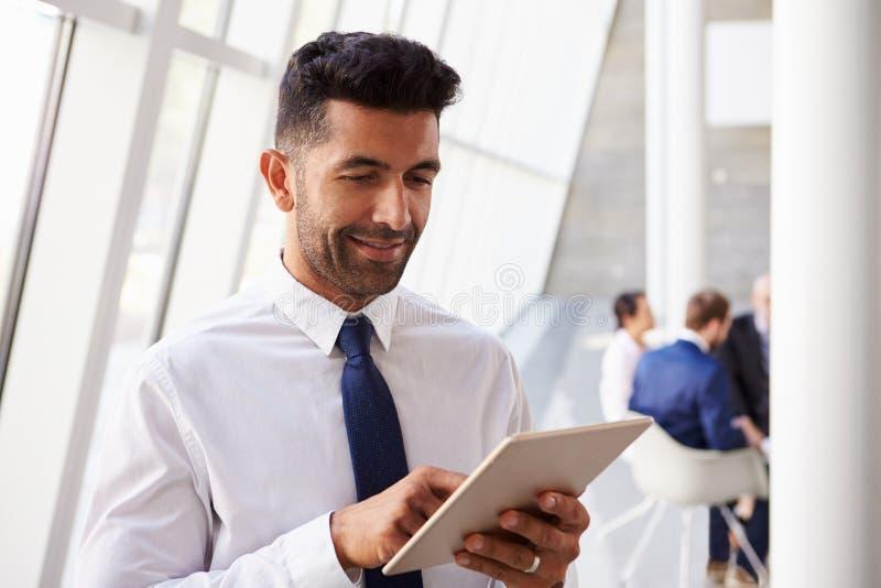 Homem de negócios latino-americano Using Digital Tablet no escritório moderno foto de stock royalty free