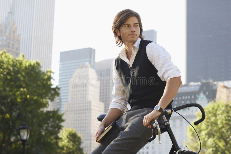 Homem de negócios Leaning On Bicycle no parque da cidade fotos de stock