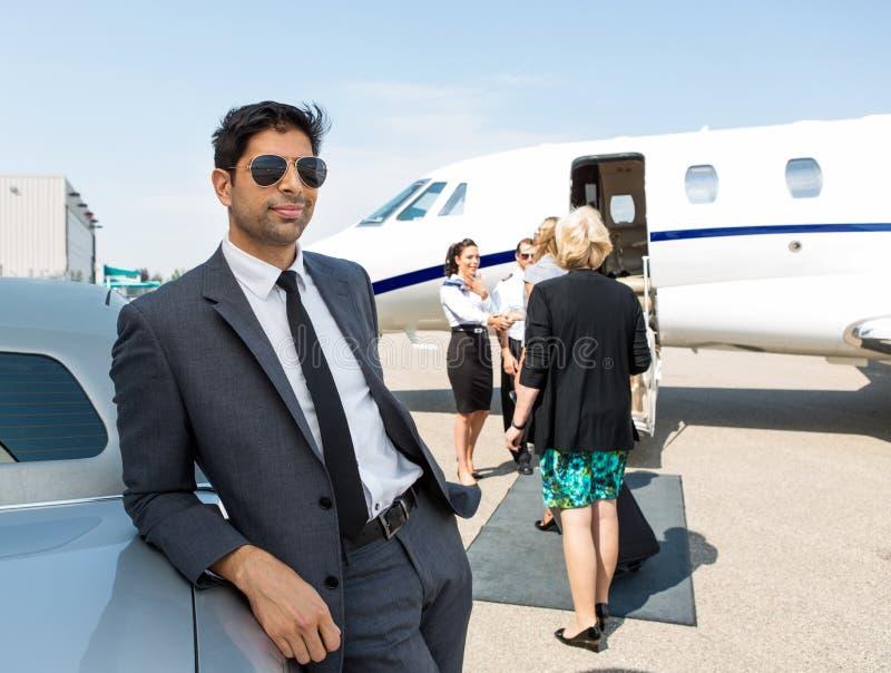 Homem de negócios Leaning On Car no terminal de aeroporto imagem de stock royalty free