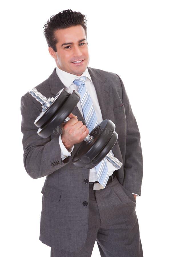 Homem de negócios Lifting Dumbbells fotografia de stock