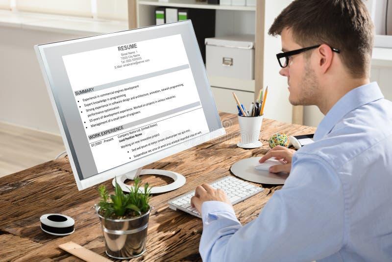Homem de negócios Looking At Resume no computador fotos de stock royalty free