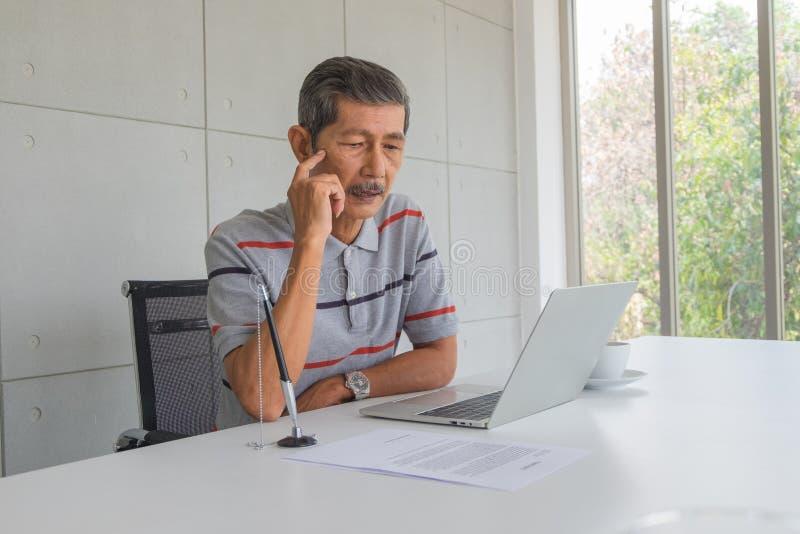 Homem de negócios maduro asiático, olhando e usando algumas ideias imagens de stock