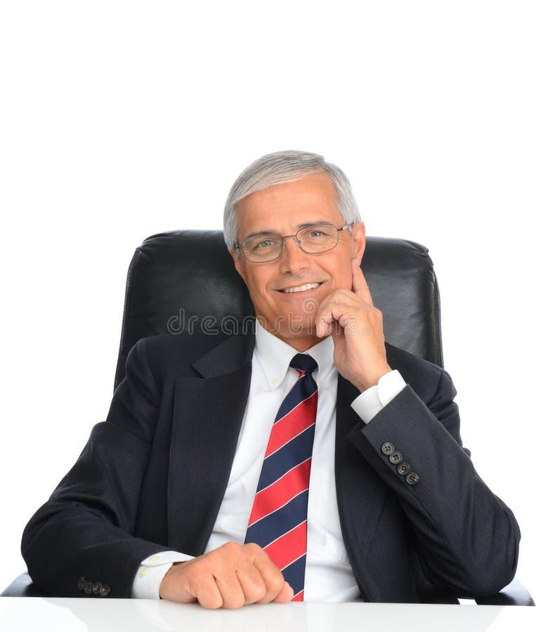 Homem de negócios maduro assentado na mesa fotografia de stock royalty free
