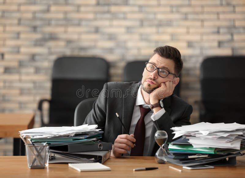 Homem de negócios maduro cansado na tabela no escritório Conceito da gest?o de tempo foto de stock