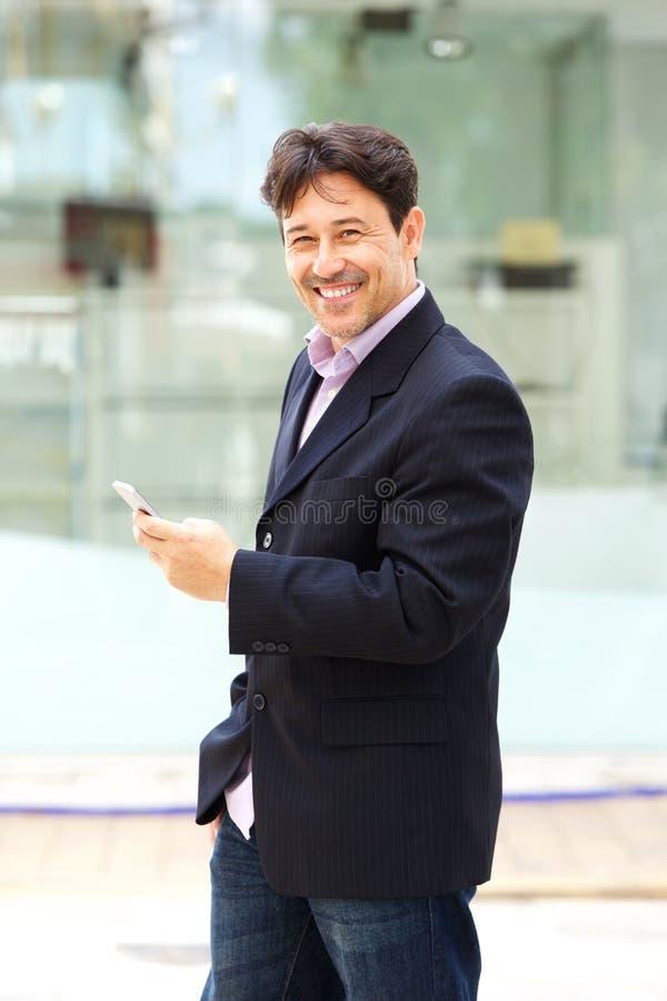 Homem de negócios maduro considerável com parte externa ereta do telefone celular fotografia de stock