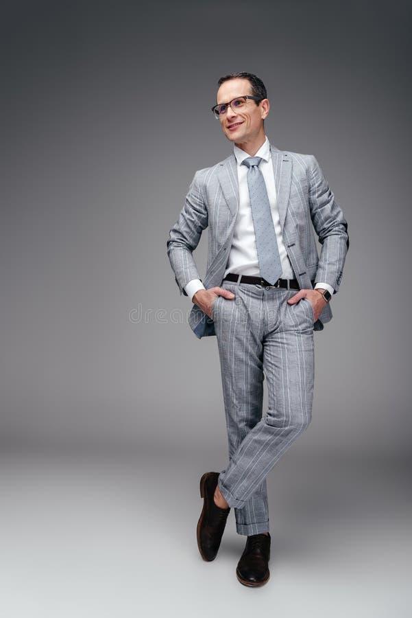 homem de negócios maduro considerável no terno à moda com mãos em uns bolsos imagem de stock