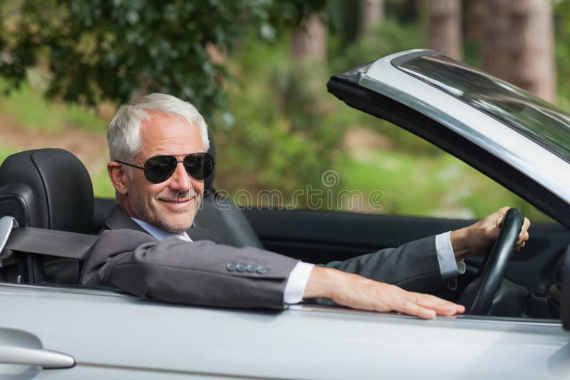 Homem de negócios maduro de sorriso que conduz o cabriolet elegante fotografia de stock royalty free