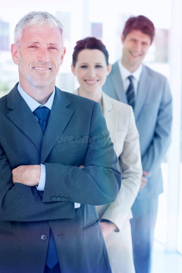 Homem de negócios maduro de sorriso que está ereto na frente de sua equipe nova fotografia de stock royalty free
