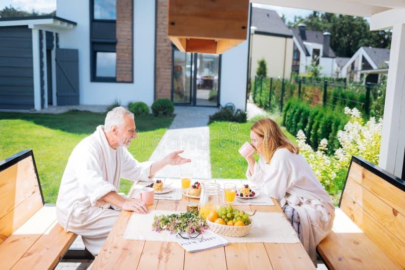 Homem de negócios maduro farpado que come o café da manhã com sua esposa atraente imagem de stock