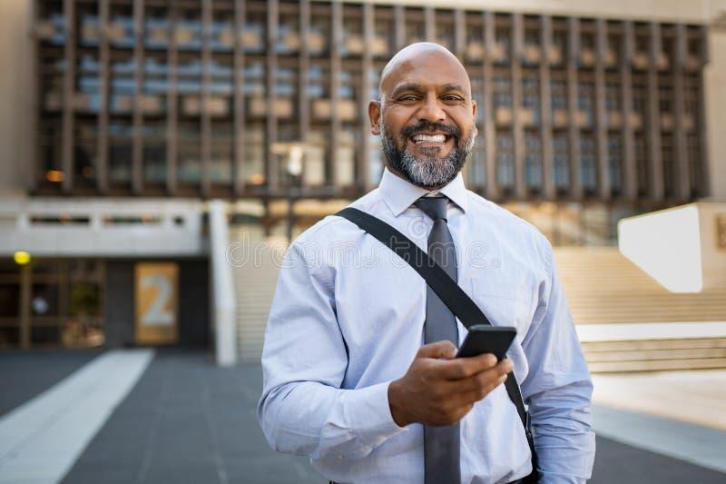 Homem de negócios maduro feliz que usa o telefone imagem de stock royalty free