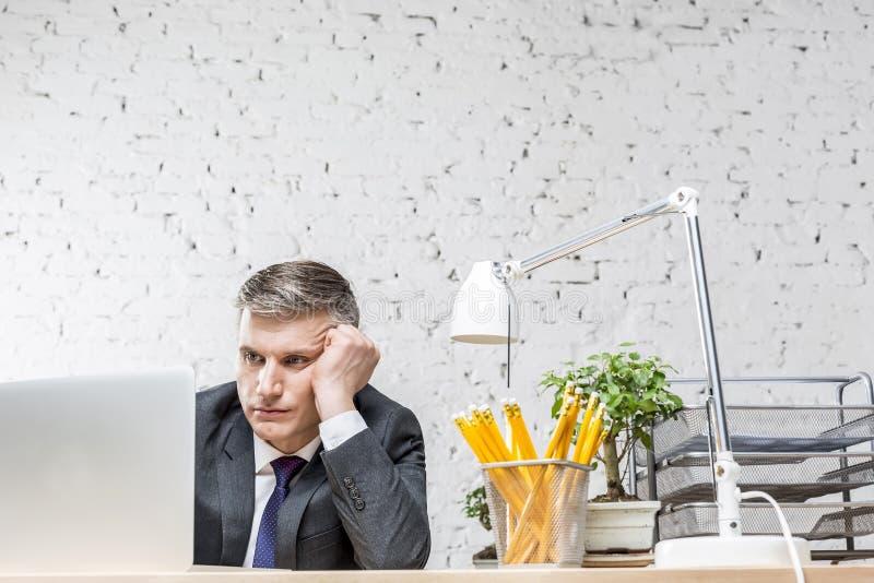 Homem de negócios maduro furado que olha o portátil na mesa contra a parede de tijolo no escritório imagem de stock royalty free