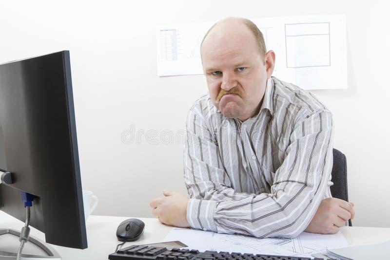Homem de negócios maduro irritado Sitting At Desk fotos de stock royalty free