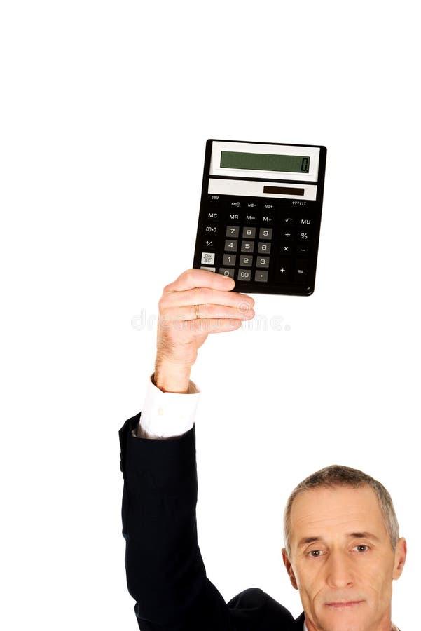 Homem de negócios maduro que guarda uma calculadora acima da cabeça fotos de stock